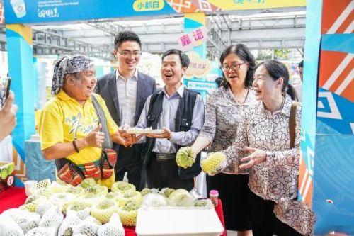 台湾歌手北原山猫吴廷宏(左一)和广西南宁市台协会长周代祥(左二)品尝台湾产的释迦果。 陈冠言 摄