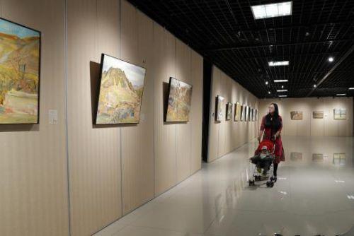 市民带着孩子观看画展。 杨迪 摄