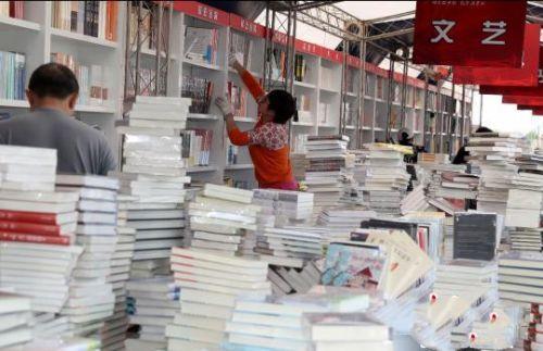 """""""北京书市""""将于4月19日至29日在朝阳公园举办。图为工作人员正在布置展区内各个书架。(完) 张宇 摄"""